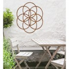 """Rustic """"Seed of Life"""" Steel Wall Art in Situ Outdoors by a Wooden Table and Chairs Set"""