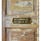 """No Hawkers No Circulars"" Sign in  Situ on a Rustic Wooden Surface"