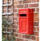 Traditional Red & Gold Wall Mounted Post Box on the Front of a House
