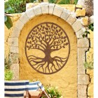 "Rustic Round ""Tree of Life"" Wall Art on a Yellow Garden Wall"