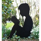 Metal Boy Reading Silhouette in situ in The Garden