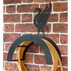 Wall Mounted Liver Bird Iron Hose Holder Mounted to a Brick Wall