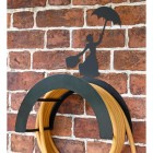 Wall Mounted Mary Poppins Iron Hose Holder Mounted to a Brick Wall