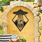 """""""I Want to Believe"""" Alien Wall Art on a Yellow Brick Wall in the Garden"""
