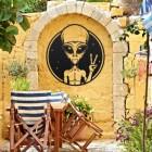 Peace Sign Alien Wall Art in Situ on a Yellow Garden Wall
