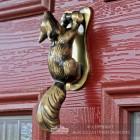 Antique Brass Squirrel door knocker on red door
