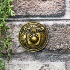 Traditional lion face bell push on brick wall