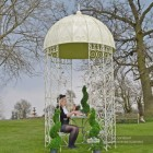 Ornate tradtional gazebo in garden with solid roof