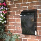 Newspaper post box mounted on wall