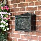 Black ornate post box on brick wall