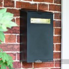 Black and Brass Newspaper Box On Brick Wall