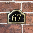 Vinyl Black & Brass Arched Number Sign in Situ on a Brick Wall