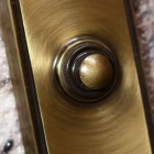Close up of antique bronze finish and chime push button