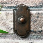 Arched burnished copper door bell on brick wall