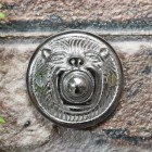 Bright Chrome bell push on brick wall