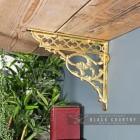 Brass Serpent Design Shelf Bracket in Situ Holding Up a Wooden Shelf