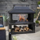Large Wood Burner and Log Store in Use in the Garden