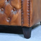 Close-up of the Feet on the Brown Leather Traditional Arm Chair