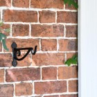Black Scroll Iron Hanging Basket Bracket on Brick Wall