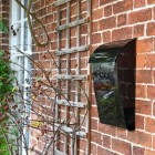 """""""Cityscape"""" Black Contemporary Post Box With Lock and Newspaper Holder in Situ on the Front of a House"""