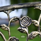 Close Up Of Rose Detailing On Black and Bronze Bench