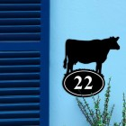 Cow Iron House Number Sign on a Blue Wall