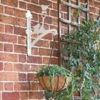 Cream Robin Hanging Basket Bracket Holding a Flower Basket Outdoors