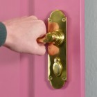 Polished Brass 6 Inch Lever Lock Handles on Pink Door in Use