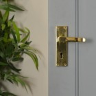 Polished Brass Lever Handle With Key Hole in Situ on Grey Door