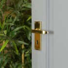 Polished Brass Lever Handle With Key Hole on Open Grey Door