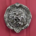 large round Bright Chrome Sandringham door knocker on red door