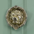 Polsihed Brass round Regal lion door knocker on Pastel green door