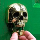 Scale image of polished brass skull door knocker