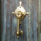 Polished Brass Turnbrook Park door knocker on Old Wooden Door