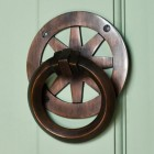 Contemporary round door knocker on green door