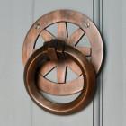 Modern antique copper round door knocker on Grey door
