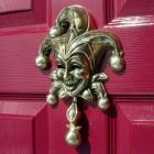 Polished brass jester Door knocker on red door