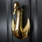 Swan door knocker mounted on black door