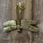 Dragon fly door knocker mounted on brown door