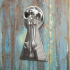 Bright chrome Key shape door knocker on rustic door