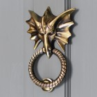 Brass dragon door knocker on grey door