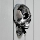 Side view of bright chrome skull door knocker