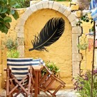 Feather Wall Art in Use on a Yellow Garden Wall
