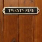 The Number Twenty Nine Displayed on the Black & Brass Gate Number Sign on a Wooden Door