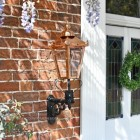 Genuine copper lantern on cast iron bracket mounted by front door