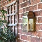 """Heathfield"" Antique Brass Half Wall Lantern on the Front of a House"