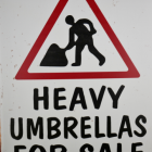 """Close-up of the """"Heavy Umbrellas For Sale"""" Sign"""