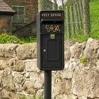 King George Rex Black Period Post Box by a Stone Wall