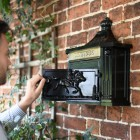 Black Post box mounted on wall with door open