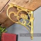 "Polished Brass ""Lotus Flower"" Shelf Bracket Holding up a Wooden Shelf"